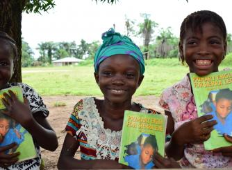 Aminata in the Middle displaying one of the text books they use for the Reading Circle.