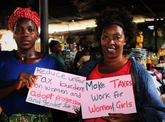 Chairlady and Market Woman pose with Placards during the sensitization on Tax